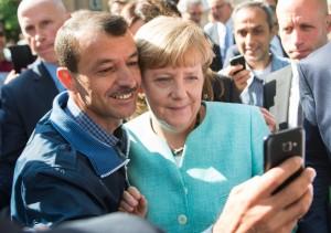 Bundeskanzlerin Angela Merkel (CDU) lässt sich am 10.09.2015 mit einem Flüchtling fotografieren. Foto: Bernd von Jutrczenka/dpa